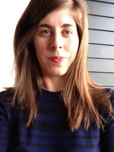 Woman with long brown hair in dark top