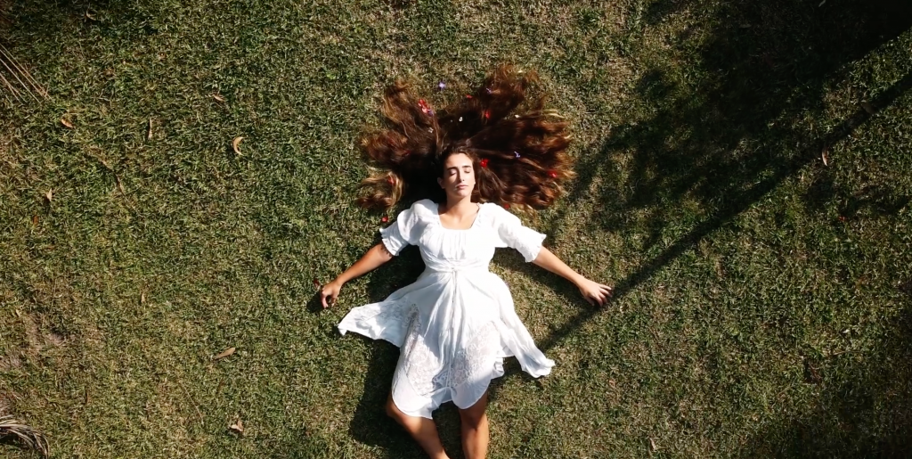 Woman in white dress seen from above lying on grass field her long hair spread around her head and decorated with coloured beads.